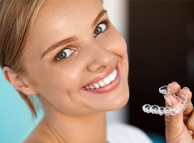 woman with straight smile holding aligners