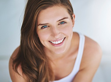 woman in white tank smiling