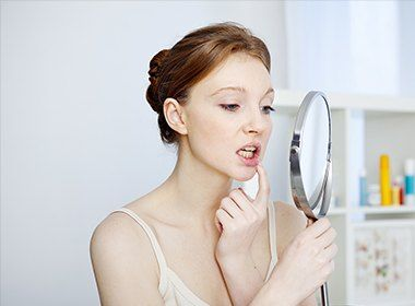 woman sadly checking smile in mirror