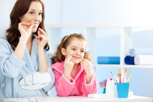 mother and daughter learning to floss using tips from their whitehall dentist