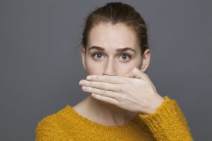 woman bad breath covering mouth