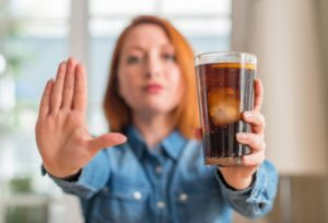 "Woman holding soda and doing ""stop"" sign with other hand"