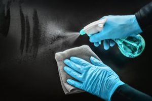dental assistant disinfecting a surface