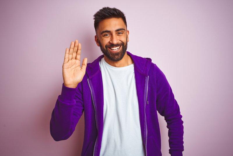Man smiling and waving