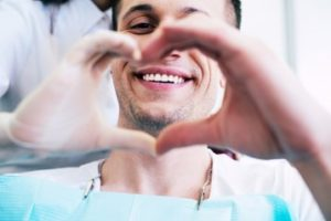 Man smiling and making half of a heart shape with his hand while a gloved hand makes the other half of the heart