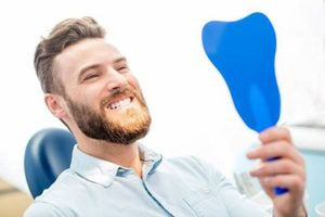 Man with healthy smile looking in dental mirror