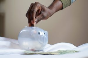 Man placing coin in clear piggy bank